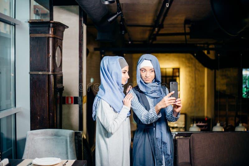 Excited молодые мусульманские подруги принимая selfie совместно стоковое изображение rf
