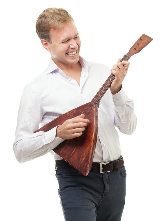 Excited молодой человек играя балалайку, изолированную дальше стоковые фото
