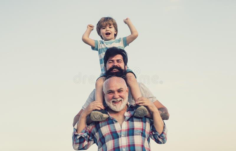 excited Отец и сын играя outdoors Счастливый усмехаясь мальчик на папе плеча смотря камеру E 3 люд стоковая фотография rf