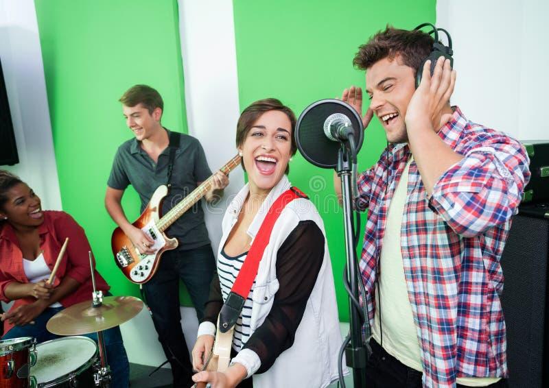 Excited певицы выполняя пока коллеги играя музыкальное Inst стоковое фото
