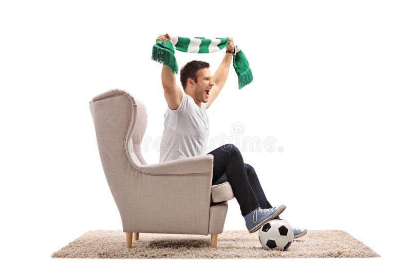 Excited поклонник футбола с футболом и веселить шарфа стоковая фотография