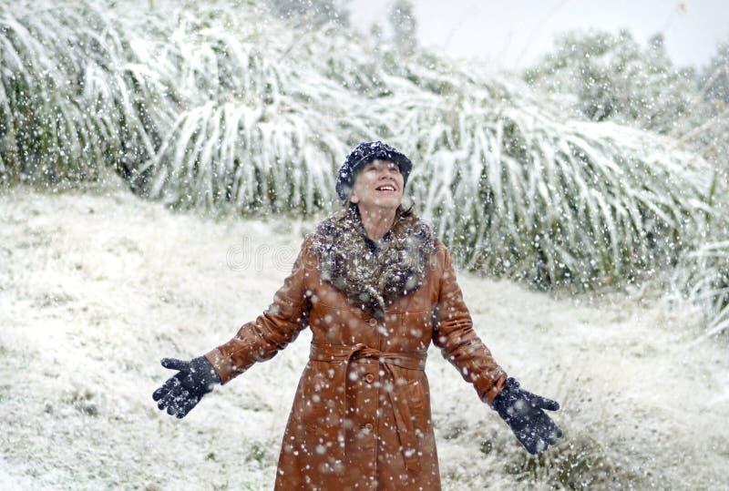 Excited радостная женщина стоя в падая снеге на первый раз в жизни стоковые изображения