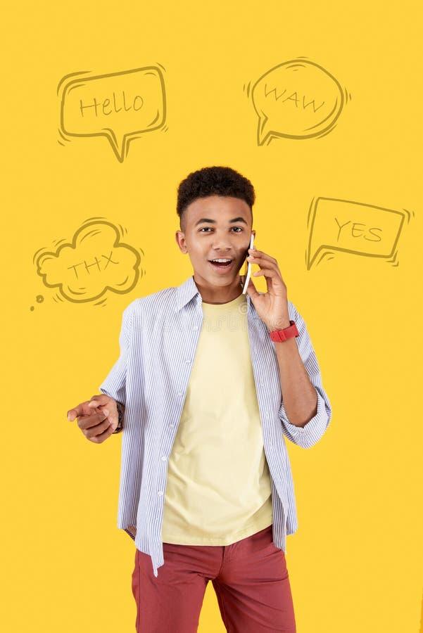 Excited студент слыша чудесные новости пока говорящ на телефоне стоковые изображения