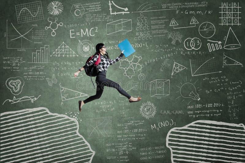 Excited студент скача на зазор стоковое изображение rf