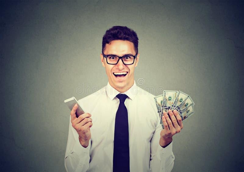 Excited счастливый профессиональный бизнесмен держа наличные деньги доллара мобильного телефона и денег стоковое фото rf