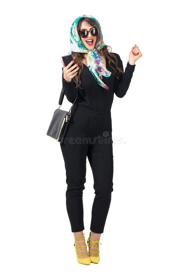 Excited счастливая женщина с головным платком и солнечные очки при открытый рот держа мобильный телефон стоковое фото