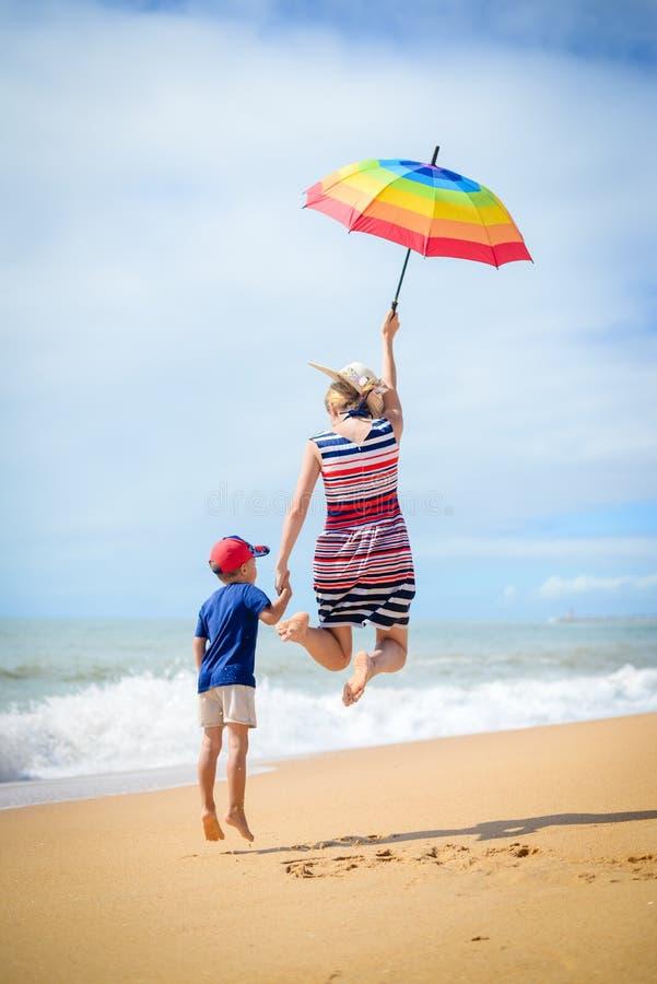 Excited сын матери имеет скачку потехи на солнечной предпосылке пляжа outdoors стоковое изображение rf