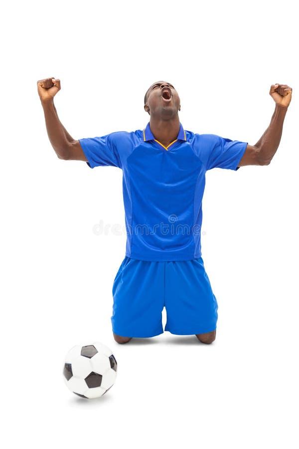 Excited футболист в голубой веселить на его коленях стоковое фото