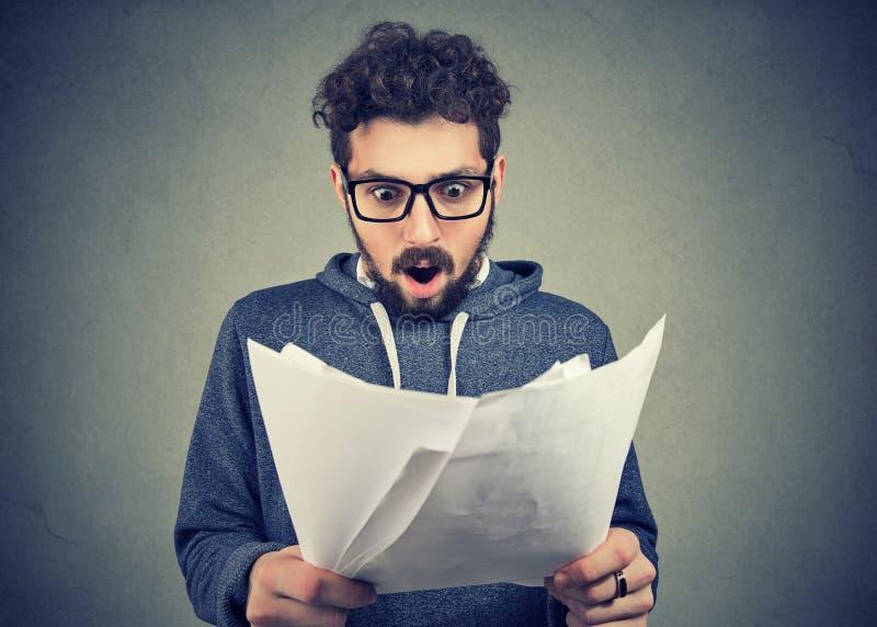 Excited человек смотря бумаги в ударе стоковые изображения