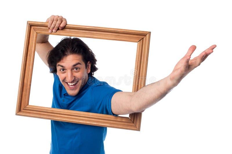 Excited человек держа картинную рамку стоковая фотография rf