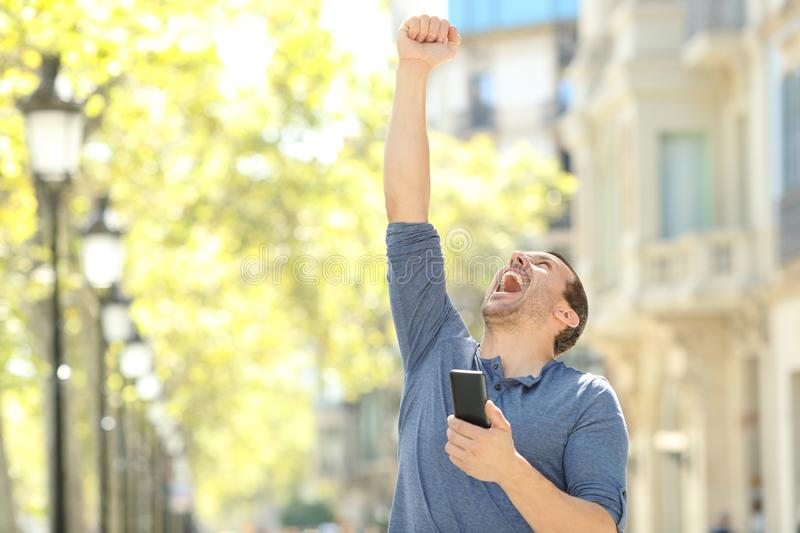 Excited adult man holding phone celebrating success. Excited adult man holding mobile phone celebrating success raising arm in the street stock image