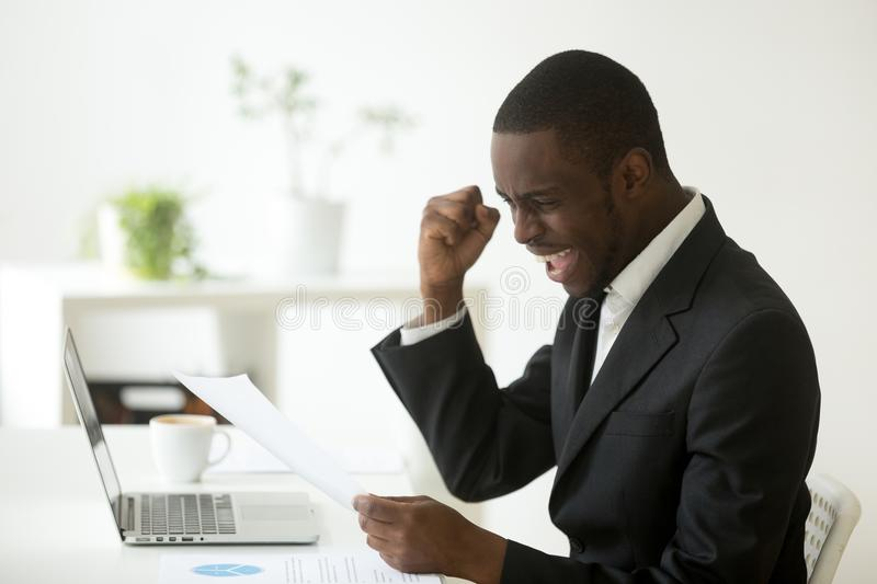 Excited african american businessman reading letter with unexpec royalty free stock photography