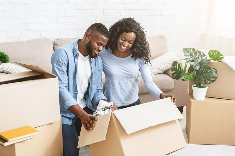 Excited african american couple unpacking stuff after moving in. Moving concept. Excited african couple unpacking stuff, holding paper boxes, copy space royalty free stock photography