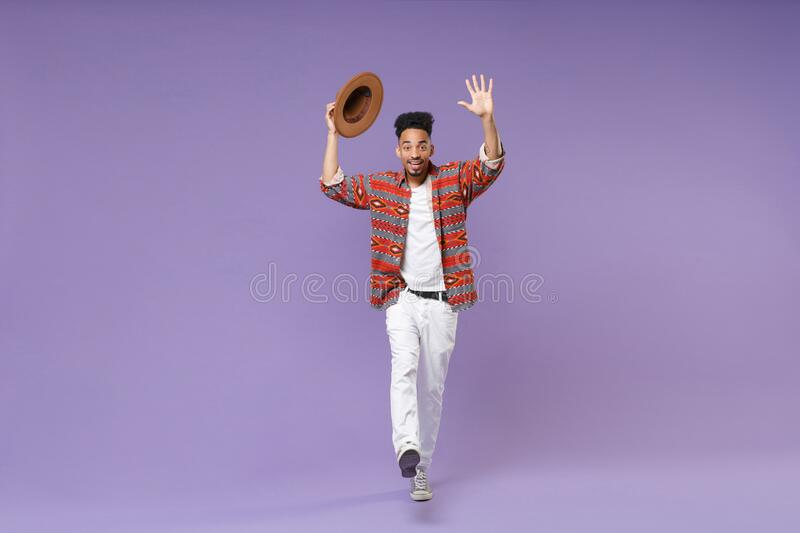 Excited african american guy in colorful shirt hat isolated on violet background. People lifestyle concept. Mock up copy royalty free stock photography