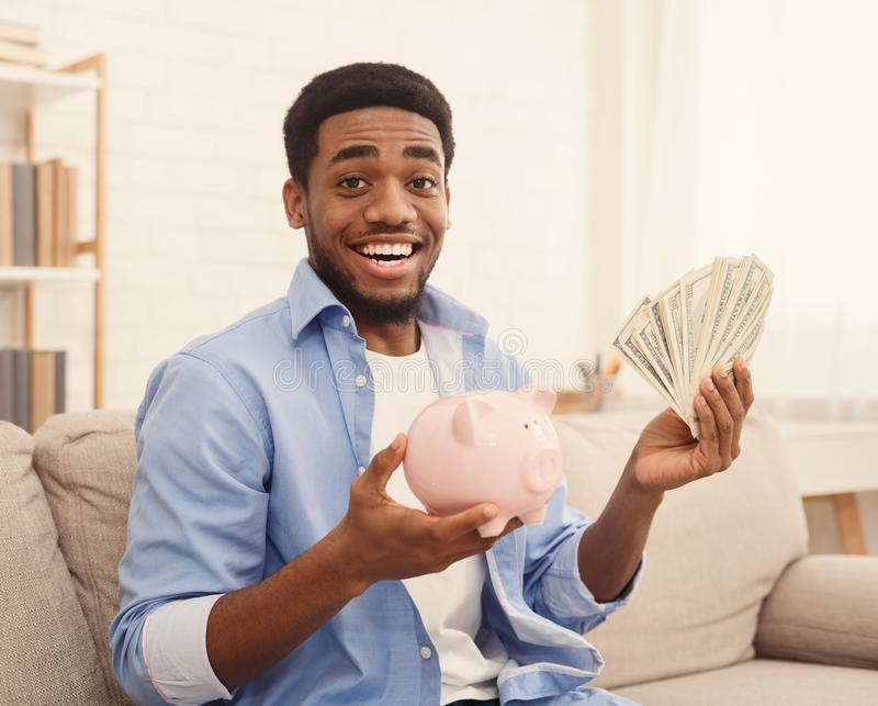Excited african-american guy holding piggybank and dollar bills royalty free stock photos