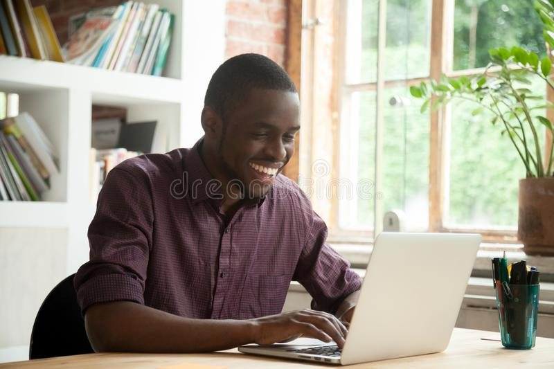 Excited African American happy with good business news. Excited African American guy surprised with good online news about growing rates at stock exchange market stock images
