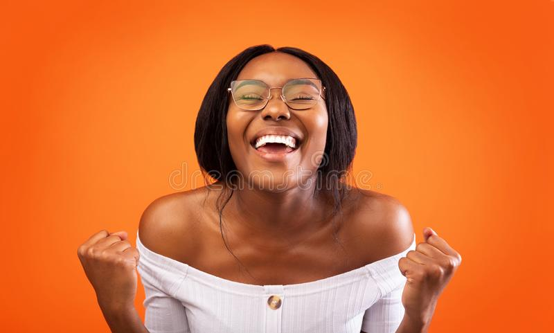 Excited African American Lady Gesturing Yes Standing Over Orange Background. Joy Of Victory. Excited African American Lady Shaking Fists Gesturing Yes Standing stock image