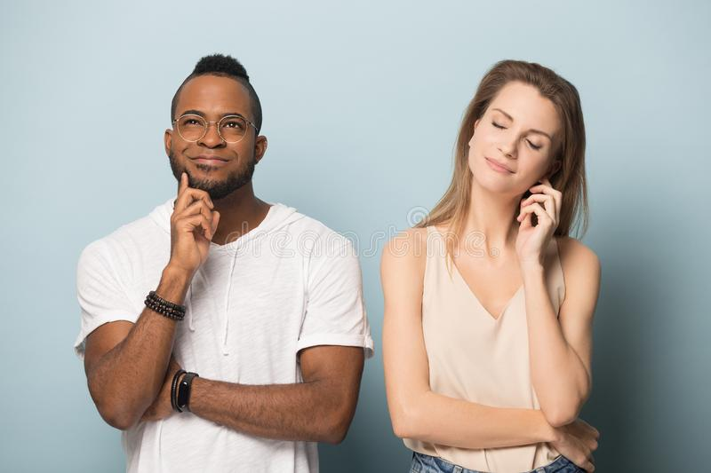 Excited multiracial man and woman hope for luck. Excited african American men and Caucasian women isolated on blue studio background join hands grateful for good stock image