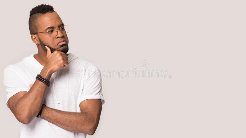 Excited black man scream at blank copy space in studio. Excited african American man in glasses isolated on grey studio background shout at blank copy space royalty free stock image