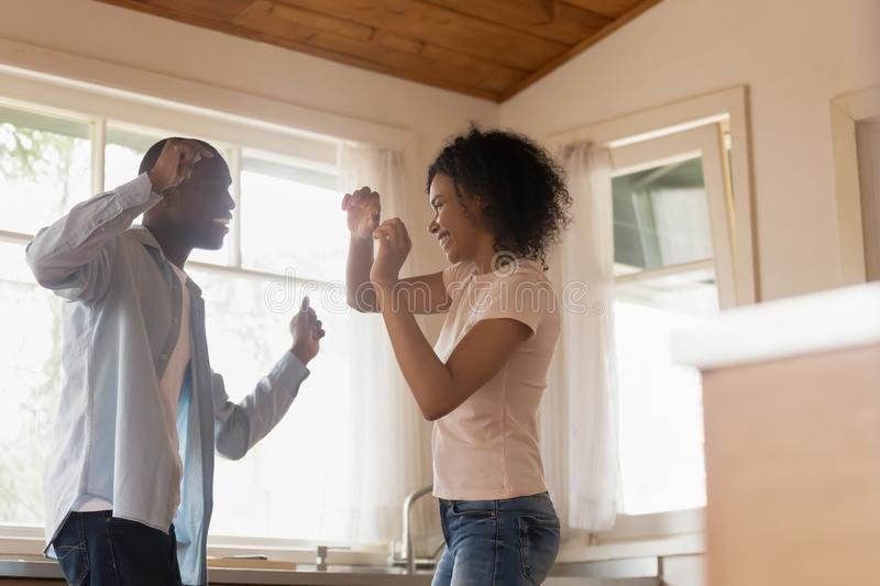 Happy biracial couple dancing in kitchen celebrating relocation. Excited african American millennial husband and wife have fun celebrating anniversary at home stock photos