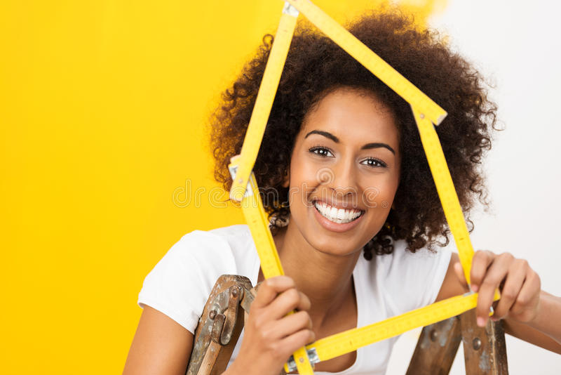 Excited African American woman in her new home. Holding up a wooden frame in the shape of a house stock photography