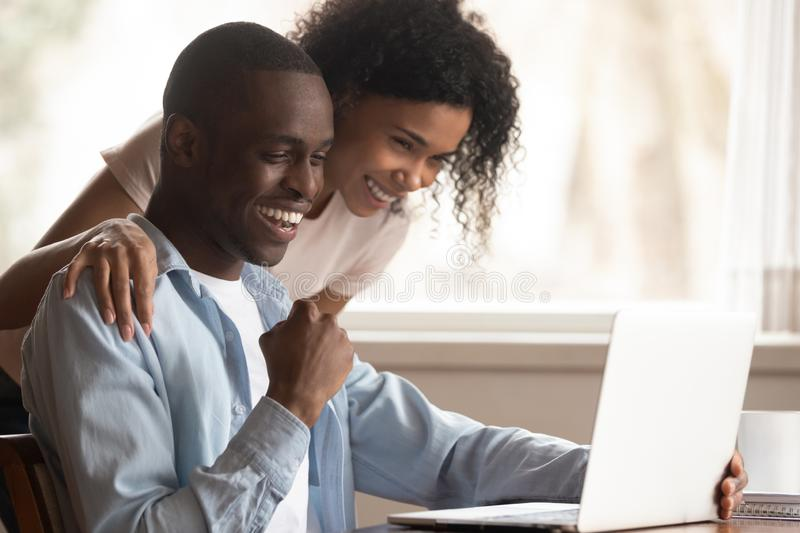 Excited biracial couple triumph win lottery on laptop online. Excited african American young couple look at laptop screen triumph win lottery online, overjoyed stock photo