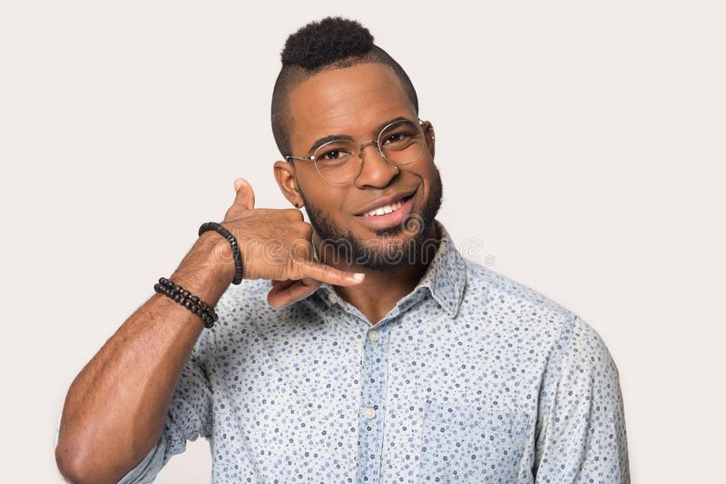 Happy black young man laugh isolated on grey background. Excited african American young man in glasses and sport clothes isolated on grey background laugh stock photo