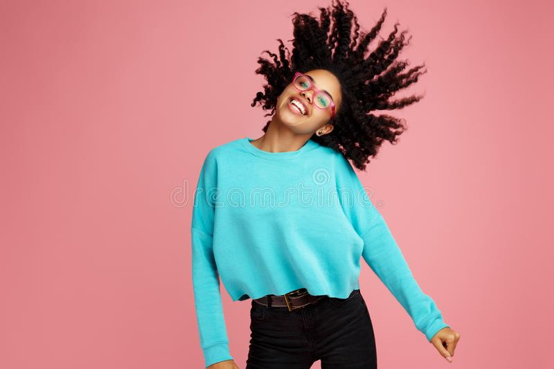 Excited african american young woman with bright smile dressed in casual clothes, glasses and headphones dance over pink stock image