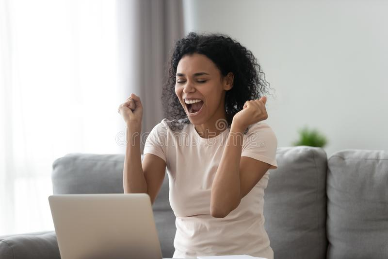 Excited african girl student winner celebrating victory looking at laptop royalty free stock images
