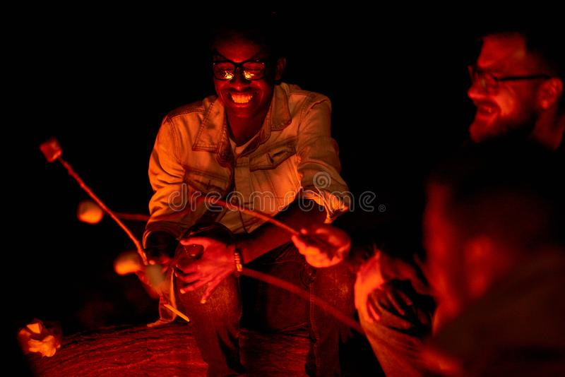 Excited African guy cooking marshmallow on campfire with friends stock images
