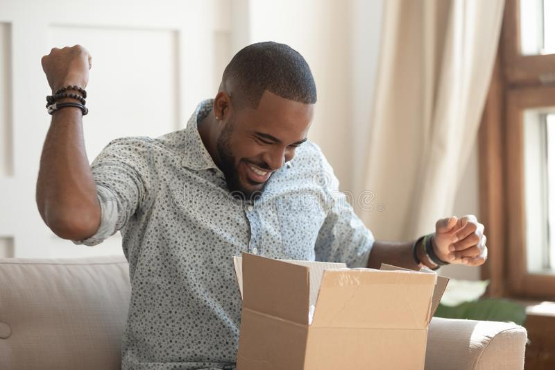 Excited african man customer receive open parcel box at home. Excited african man customer receive good parcel open cardboard box at home satisfied with great royalty free stock photography