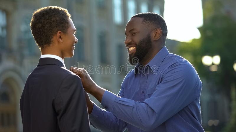 Excited african man feeling proud of young son in prom suit, college graduation stock photo