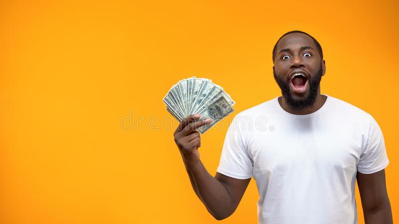 Excited Afro-American man holding bunch of dollar, crowd funding or start-up royalty free stock photos