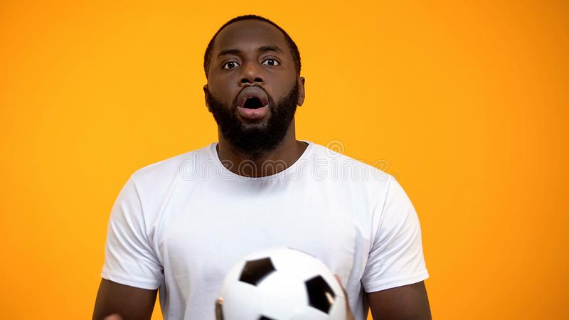 Excited Afro-American man with soccer ball attentively watching football match royalty free stock photography