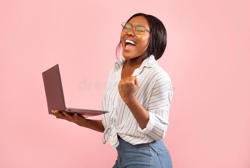 Excited Afro Girl Holding Laptop Gesturing Yes, Studio Shot stock photo