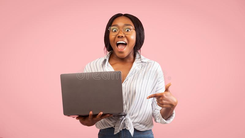 Excited Afro Girl Pointing Finger At Laptop, Pink Background, Panorama stock image