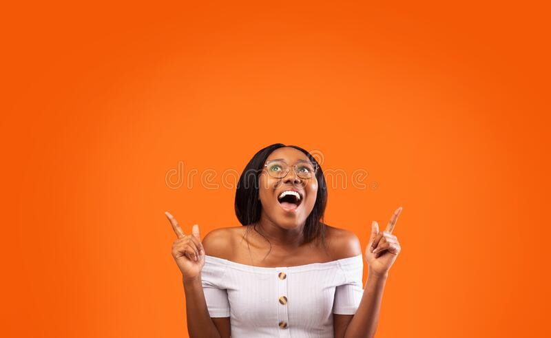 Excited Afro Lady Pointing Fingers Up At Empty Space, Studio royalty free stock image