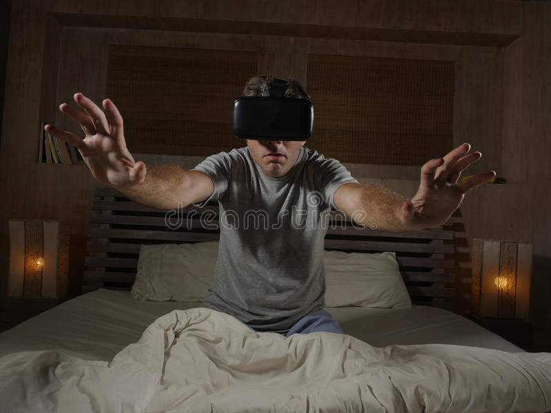 Excited and amazed man wearing VR virtual reality goggles device playing internet 3D simulator game enjoying exciting and. Young excited and amazed man wearing stock image