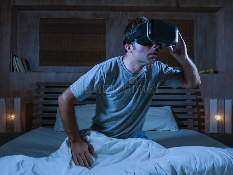 Excited and amazed man wearing VR virtual reality goggles device playing internet 3D simulator game enjoying exciting and. Young excited and amazed man wearing royalty free stock photography