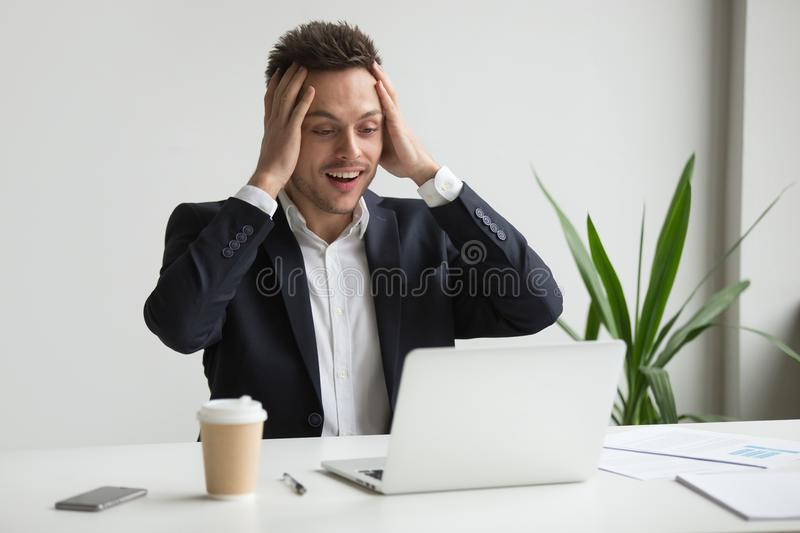 Excited amazed millennial businessman surprised by unexpected go. Excited millennial businessman surprised at unexpected good news online, astonished man in suit stock images