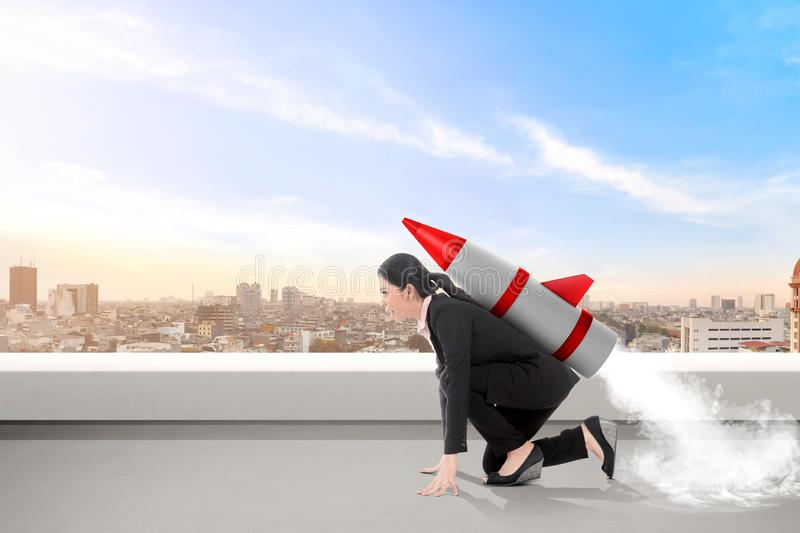 Excited asian business woman on the rooftop with rocket ready to fly royalty free stock photography
