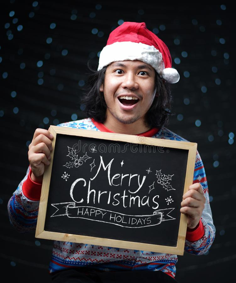 Excited Asian Man Wearing Santa Hat and Christmas Sweater Holding Merry Christmas Typography on Blackboard stock photography