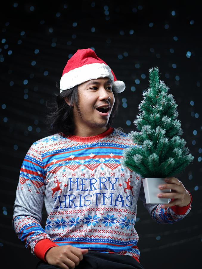 Excited Asian Man Wearing Santa Hat and Christmas Sweater Holding Small Christmas Tree royalty free stock images