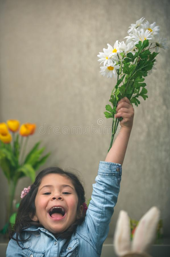 Excited baby girl with flowers stock photo