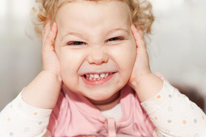 Excited baby girl leaning on her hands royalty free stock photo