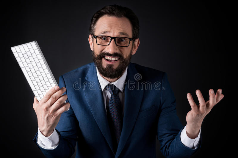 Excited bearded businessman in eyeglasses holding keyboard and looking at camera royalty free stock photo