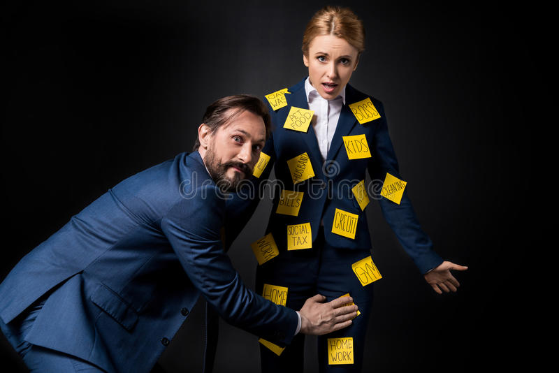 Excited bearded businessman touching frustrated businesswoman with sticky notes on clothes looking at camera stock photo