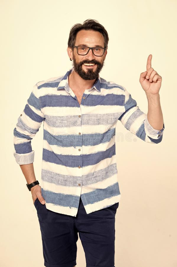 Excited bearded man with glasses holding forefinger up and looking enlightened with brilliant idea. Man points up to information. On white background stock image
