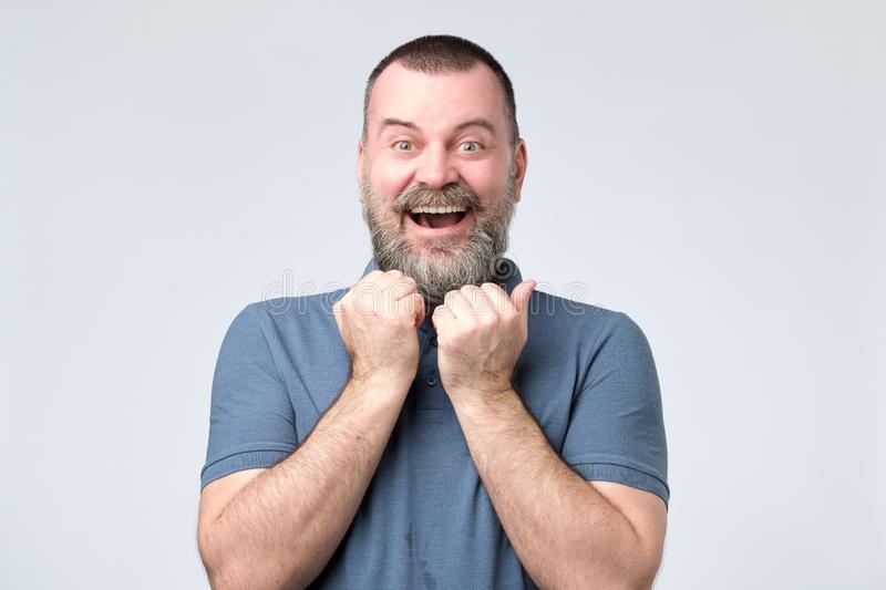 Excited bearded man standing with fists up royalty free stock photos