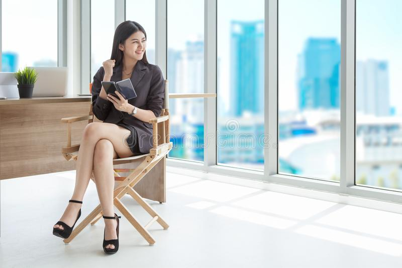Excited Beautiful asian young businesswoman receiving good news. On mobile phone to successful of agreement raised arms in office.cute Entrepreneur girl glad royalty free stock images